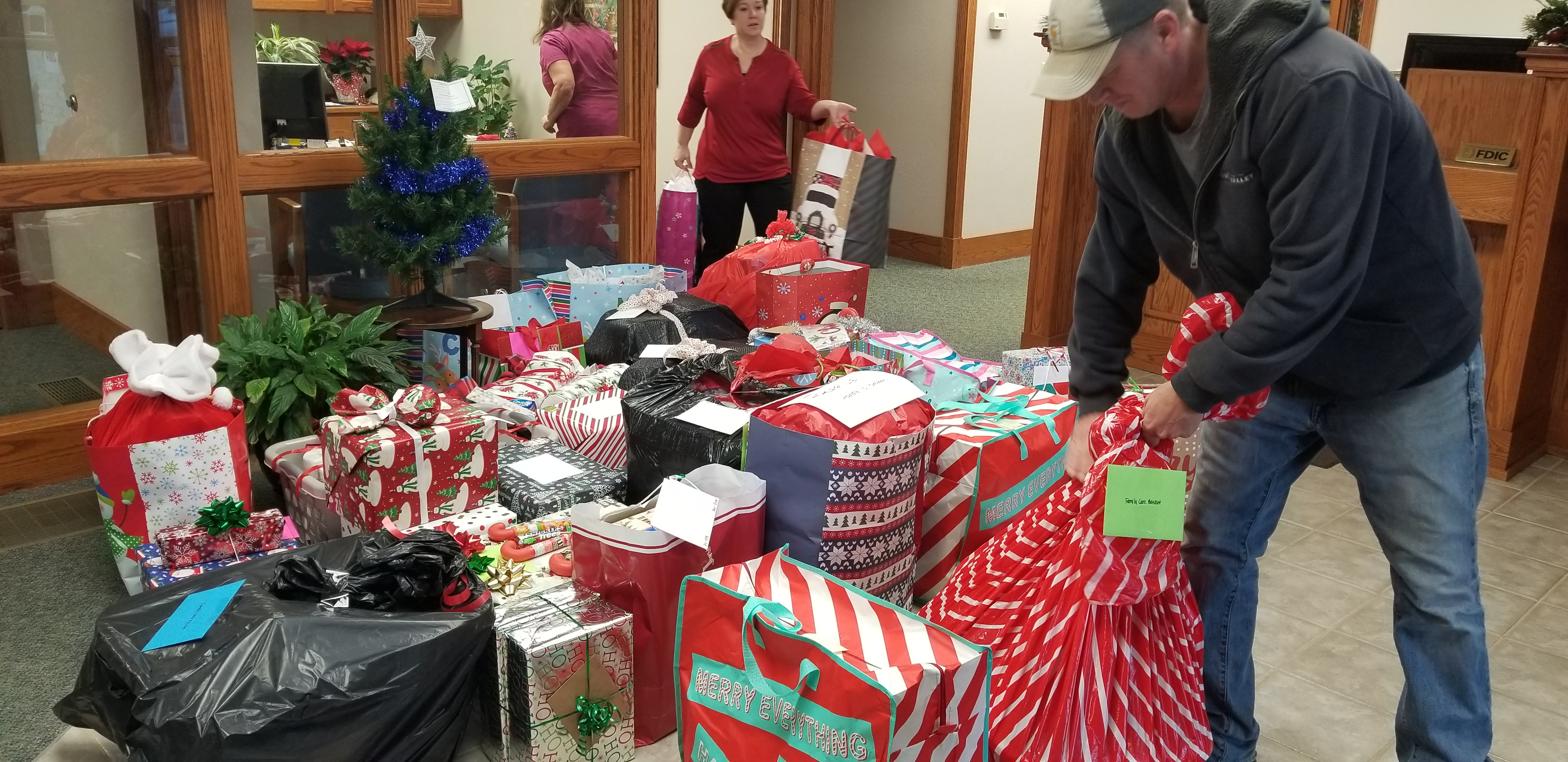 Blue Valley Telecommunications employee carries away the gifts for distribution.